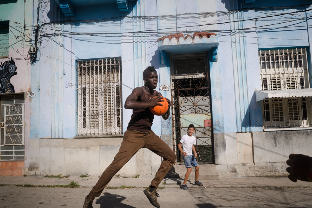 black cuban boy jumping with a basket ball , picture taken by louis alarcon in a photography tour