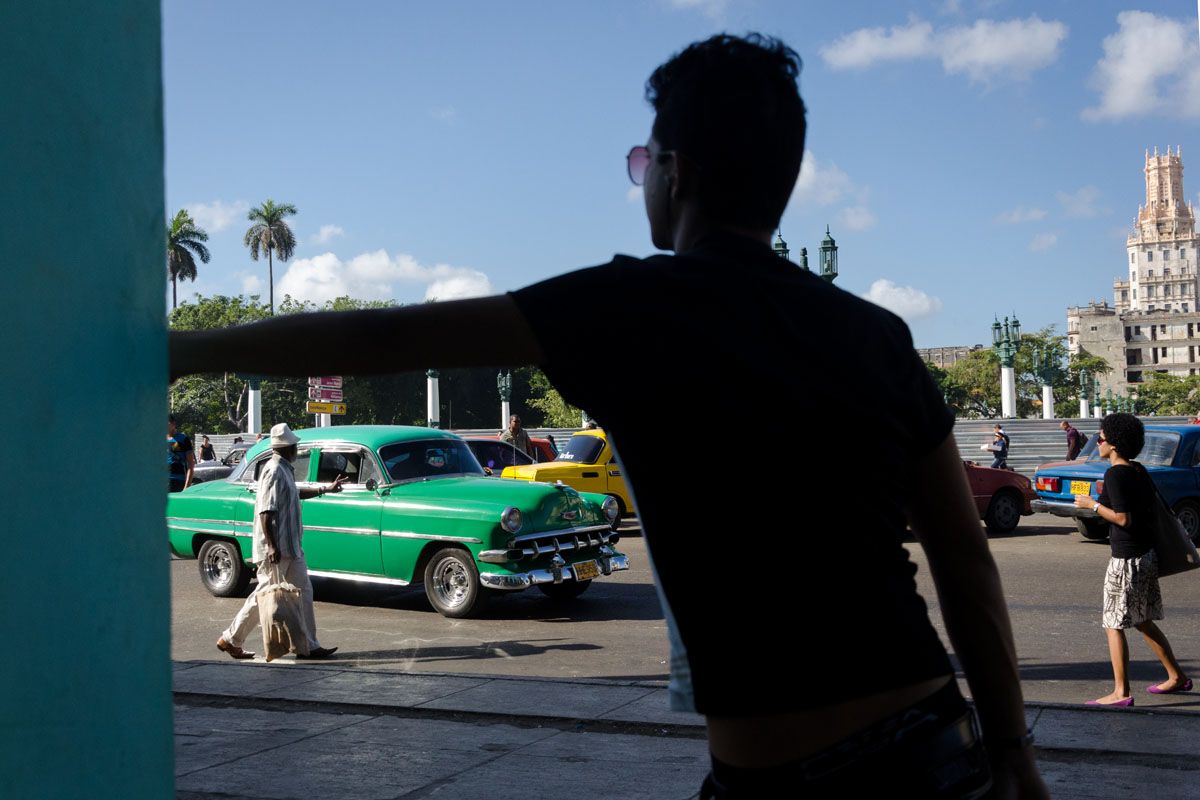 old american car through the frame of a cuban boy arm