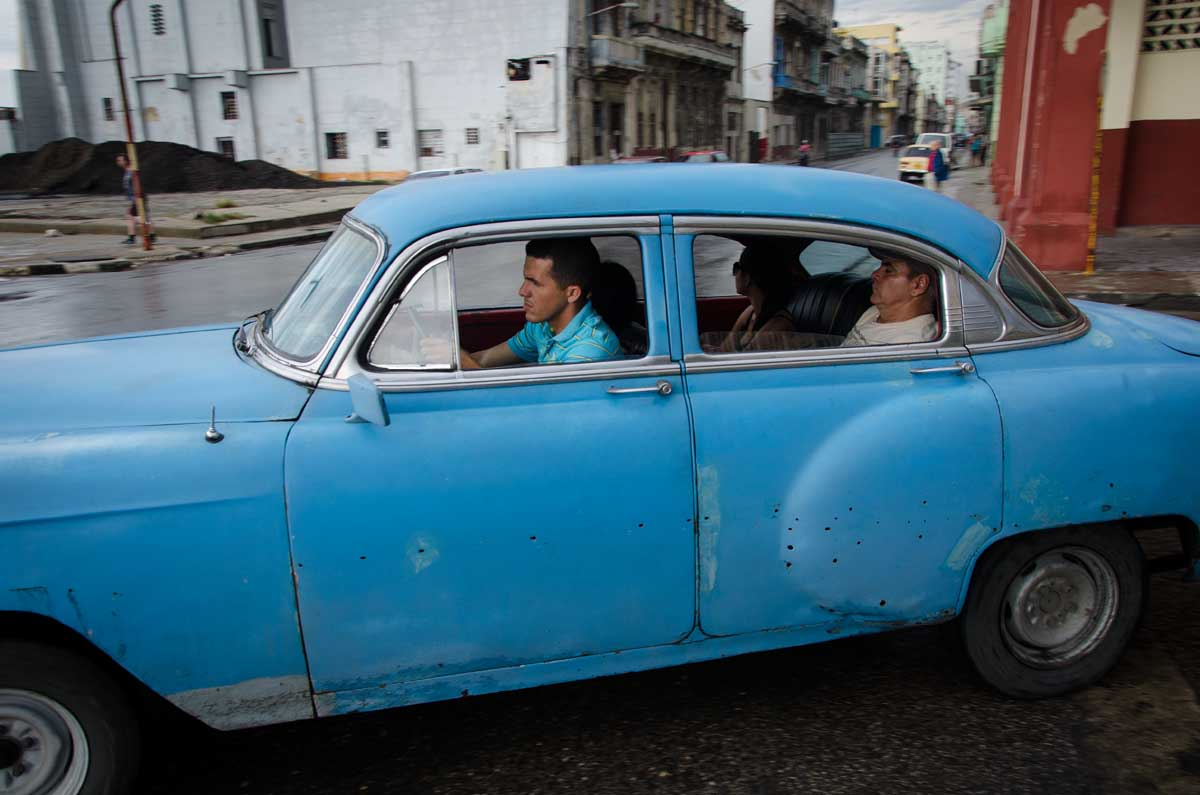 street photography in havana about an old american car with people sleeping inside