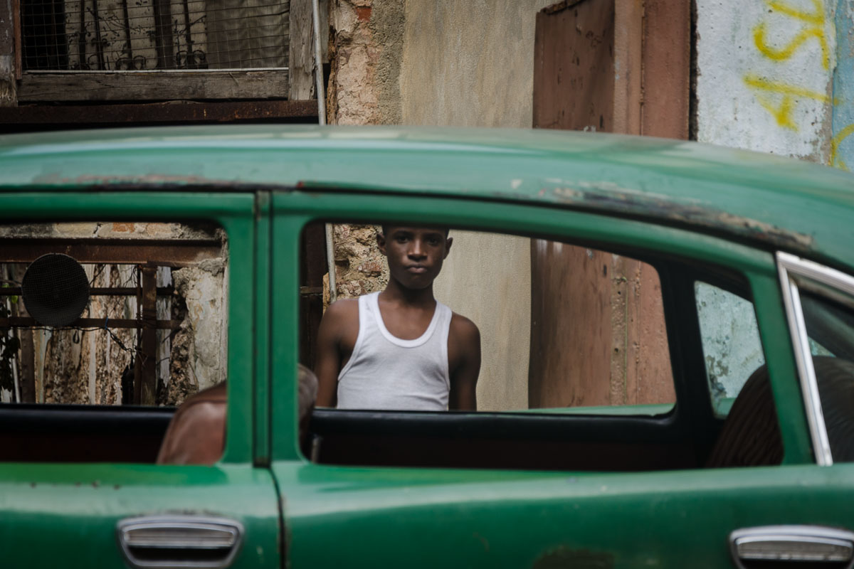 cuban boy and a green american car , practising street photography