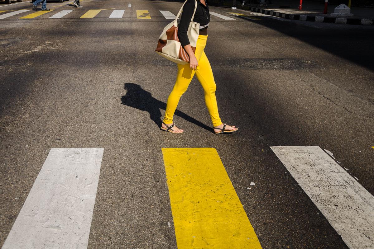 yellow cuban girl crossing a street in havana
