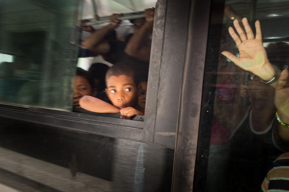 children in a bus through the window in a  photo tour in cuba