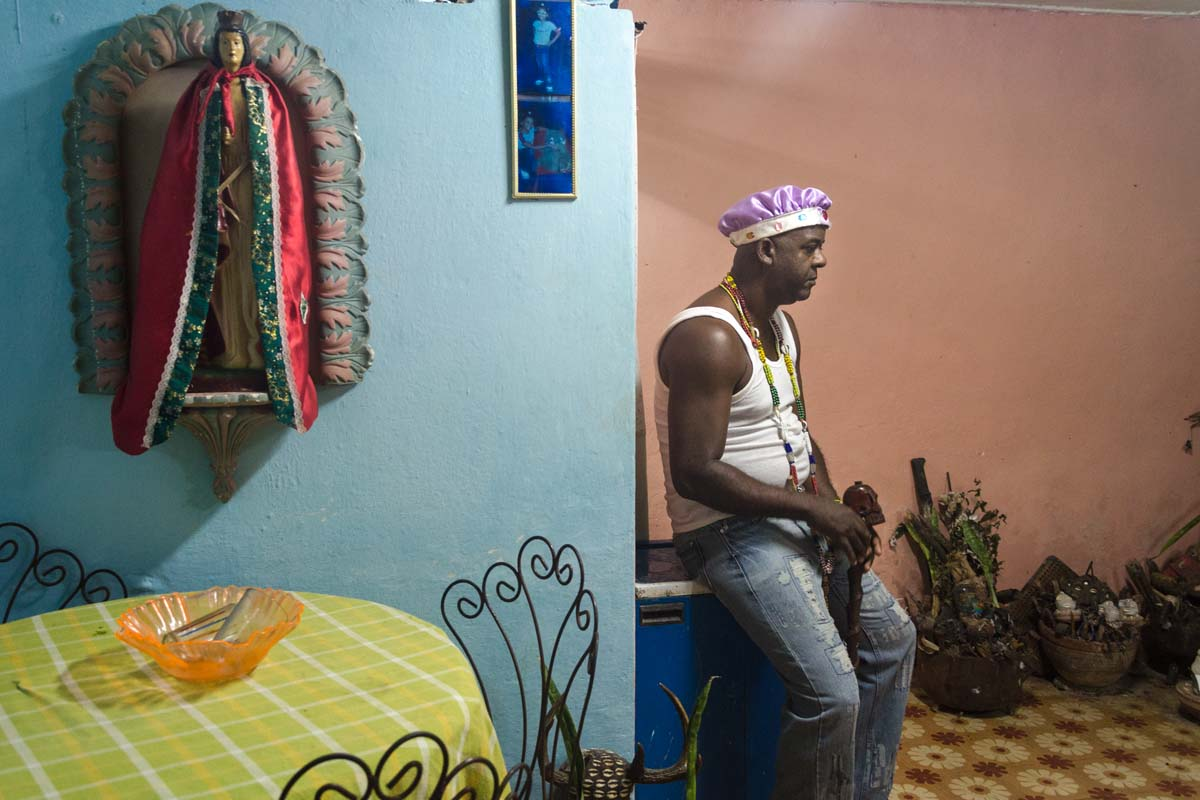 afrocuban priest in his house with saints in havana , cuban photo workshop