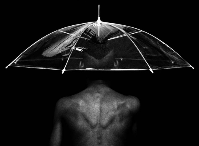 black nude man under the umbrella. Cuban photography by rene peña