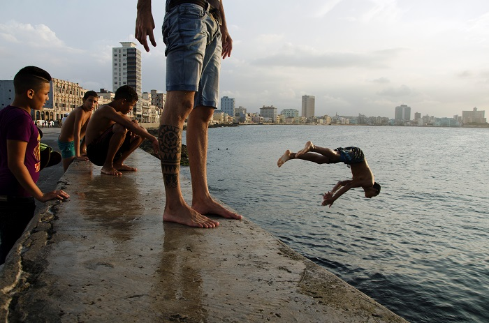 young cuban boys jumping in malecon by louis alarcon