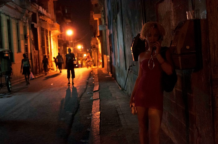 cuban woman at night calling in a public phone by louis alarcon